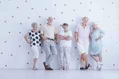 Glückliche ältere Menschen in der zufälligen Kleidung im weißen Studio mit Gold stockbilder