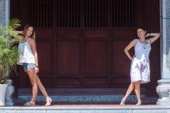 Glückliche ältere Mutter- und Erwachsentochter betrachten die Kamera und Stand und lehnen sich auf Säulen Stockfoto