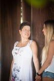 Glückliche ältere Mutter- und Erwachsentochter betrachten einander und halten Hände Lizenzfreie Stockfotografie