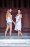 Glückliche ältere Mutter- und Erwachsentochter betrachten Kamera und halten Hände Lizenzfreies Stockfoto