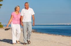 Glückliche ältere Paar-gehendes Lachen auf einem Strand lizenzfreie stockfotos