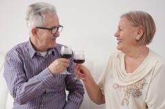 Glückliche ältere Paar-trinkender Wein zu Hause stockbilder