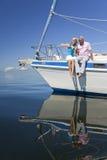 Glückliche ältere Paare auf dem Bogen eines Segel-Bootes Lizenzfreie Stockbilder