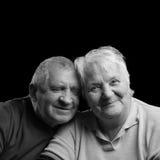 Glückliche ältere Paare auf einem schwarzen Hintergrund Stockbild