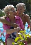 Glückliche ältere Paare auf Pool stockfoto