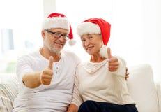 Glückliche ältere Paare in den Sankt-Helferhüten zu Hause Lizenzfreie Stockfotografie