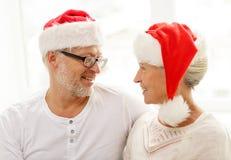 Glückliche ältere Paare in den Sankt-Helferhüten zu Hause Lizenzfreie Stockfotos