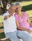 Glückliche ältere Paare, die auf Bank im Sonnenschein sitzen Lizenzfreie Stockfotos