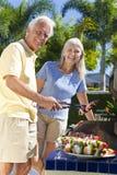 Glückliche ältere Paare, die auf einem Sommer-Grill kochen Lizenzfreie Stockfotografie