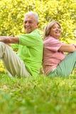 Glückliche ältere Paare, die auf Gras sitzen lizenzfreies stockfoto
