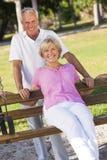 Glückliche ältere Paare, die auf Park-Bank lächeln Stockbild