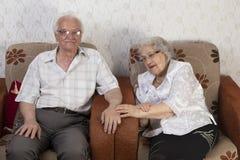 Glückliche ältere Paare, die auf Sofa sitzen Stockbild