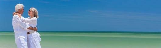 Glückliche ältere Paare, die auf tropischem Strand umfassen stockbilder