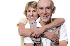 Glückliche ältere Paare, die auf Weiß umfassen Stockfoto