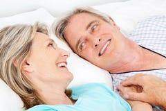 Glückliche ältere Paare, die in Bett streicheln Lizenzfreie Stockfotos