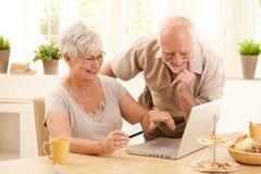 Glückliche ältere Paare, die das Onlineeinkaufen tun Stockfoto