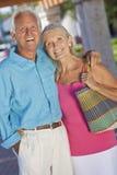 Glückliche ältere Paare, die draußen im Sonnenschein lächeln Lizenzfreies Stockfoto