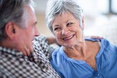 Glückliche ältere Paare, die einander und das Lächeln betrachten Stockfoto