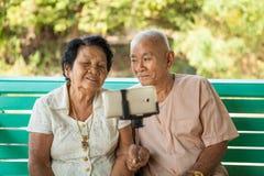 Glückliche ältere Paare, die für ein selfie aufwerfen Stockbild