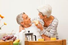 Glückliche ältere Paare, die frühstücken Stockbilder