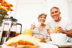 Glückliche ältere Paare, die frühstücken Lizenzfreies Stockbild
