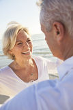 Glückliche ältere Paare, die Handtropischen Strand anhalten gehen Stockbild