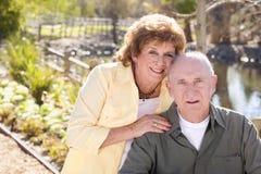 Glückliche ältere Paare, die im Park sich entspannen Stockfotos