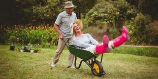 Glückliche ältere Paare, die mit einer Schubkarre spielen Lizenzfreie Stockfotos