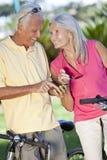 Glückliche ältere Paare, die unter Verwendung des intelligenten Telefons GPS einen Kreislauf durchmachen Stockbild