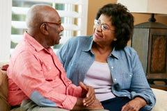 Glückliche ältere Paare, die zu Hause auf Sofa sitzen lizenzfreies stockfoto