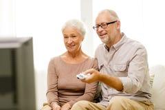 Glückliche ältere Paare, die zu Hause fernsehen Stockbilder