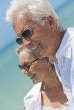 Glückliche ältere Paare, die zum Meer auf einem Strand schauen Stockfoto