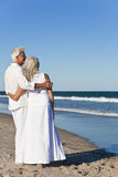 Glückliche ältere Paare, die zum Meer auf einem Strand schauen Lizenzfreies Stockfoto