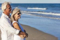 Glückliche ältere Paare, die zum Meer auf einem tropischen Strand schauen stockfoto