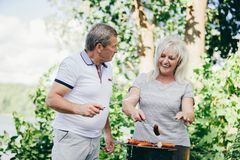 Glückliche ältere Paare, die zusammen barbequing sind Lizenzfreie Stockfotos