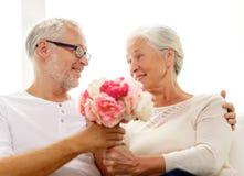 Glückliche ältere Paare mit Blumenstrauß zu Hause Stockfoto