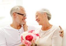 Glückliche ältere Paare mit Blumenstrauß zu Hause Lizenzfreies Stockbild