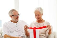 Glückliche ältere Paare mit Geschenkbox zu Hause Lizenzfreies Stockfoto