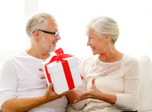 Glückliche ältere Paare mit Geschenkbox zu Hause Stockfotos
