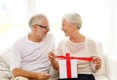 Glückliche ältere Paare mit Geschenkbox zu Hause Stockbilder