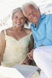 Glückliche ältere Paare mit Laptop-Computer auf Strand Stockfoto