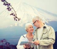 Glückliche ältere Paare mit Reise zeichnen über Bergen auf Lizenzfreies Stockfoto