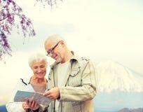Glückliche ältere Paare mit Reise zeichnen über Bergen auf Stockfotografie