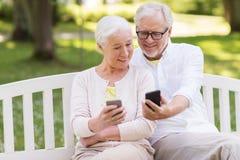 Glückliche ältere Paare mit Smartphones am Park Lizenzfreies Stockfoto