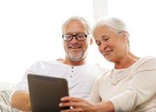Glückliche ältere Paare mit Tabletten-PC zu Hause Lizenzfreies Stockbild