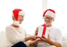 Glückliche ältere Paare in Sankt-Hüten mit Geschenkbox Stockfoto