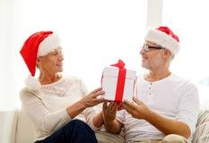 Glückliche ältere Paare in Sankt-Hüten mit Geschenkbox Lizenzfreies Stockfoto