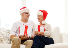 Glückliche ältere Paare in Sankt-Hüten mit Geschenkboxen Lizenzfreies Stockbild