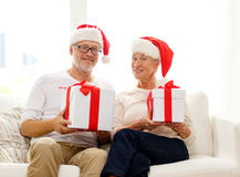 Glückliche ältere Paare in Sankt-Hüten mit Geschenkboxen Lizenzfreie Stockfotos