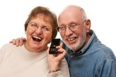Glückliche ältere Paare unter Verwendung des Handys auf Weiß Lizenzfreies Stockfoto
